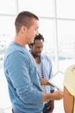 Smiling man speaking to his colleague. Smiling men speaking to his colleague in the office Stock Images