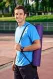 Smiling man with sport equipment. Ready to start. Young smiling man standing on stadium with his own sport equipment Royalty Free Stock Images
