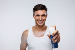 Smiling man spraying deodorant Royalty Free Stock Image