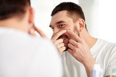Smiling man squeezing pimple at bathroom mirror. Beauty, hygiene, skin problem and people concept - smiling young man looking to mirror and squeezing pimple at royalty free stock photo