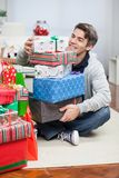 Smiling Man With Stack Of Christmas Gifts Stock Images