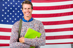 Smiling man standing against American flag Stock Images