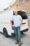 Smiling man standing against delivery van Stock Images