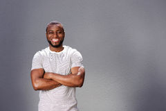 Smiling man  standing with arms crossed against gray background Stock Photos