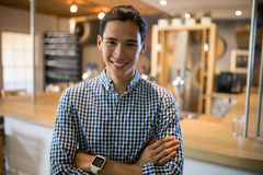 Smiling man standing with arms crossed at counter in restaurant Stock Photo