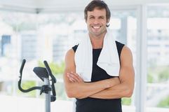 Smiling man standing with arms crossed at spinning class in bright gym Stock Images