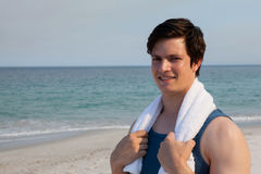 Smiling man standing on beach with towel around his neck. Portrait of smiling man standing on beach with towel around his neck Stock Photo