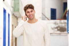 Smiling man standing on city street talking on mobile phone Royalty Free Stock Photo