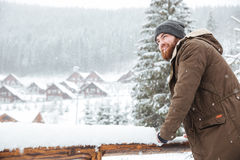 Smiling man standing and enjoying  snowy weather on winter resort Royalty Free Stock Image