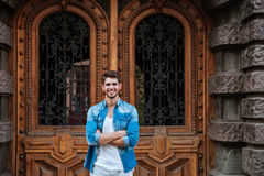 Smiling man standing in front of the beautiful wooden door. Handsome young smiling man standing in front of the beautiful wooden door waiting for someone Royalty Free Stock Photography