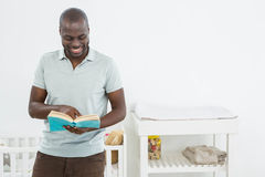 Smiling man standing in front of a cradle and reading a book. At home Stock Photos