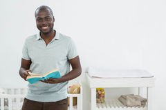 Smiling man standing in front of a cradle and reading a book. At home Royalty Free Stock Photography