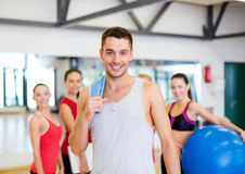 Smiling man standing in front of the group in gym Stock Photo