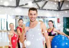 Smiling man standing in front of the group in gym Royalty Free Stock Photography