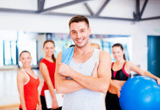 Smiling man standing in front of the group in gym Stock Photography