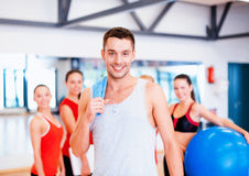Smiling man standing in front of the group in gym Royalty Free Stock Images