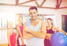 Smiling man standing in front of the group in gym Royalty Free Stock Photo