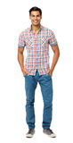 Smiling Man Standing With Hands In Pockets. Full length portrait of smiling young man standing with hands in pockets against white background. Vertical shot Royalty Free Stock Photo
