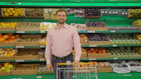 Smiling man standing with his shopping trolley on aisle at supermarket. Smiling man standing with his trolley on aisle at supermarket stock footage