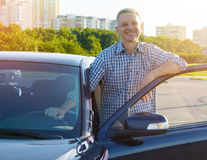 Smiling man standing and leaning on the car door stock images