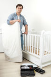Smiling man standing with mattress at disassembled baby`s cot Royalty Free Stock Photo