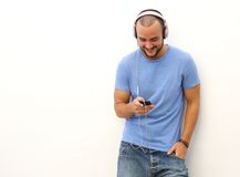 Smiling man standing with  mobile phone and headphones Stock Photography