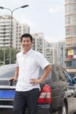 Smiling Man standing next to his car and looking at camera Stock Images