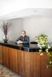 Smiling man standing at office reception. Businessman standing at reception counter in office royalty free stock photos