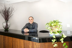 Smiling man standing at office reception. Businessman standing at reception counter in office stock photos