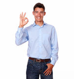 Smiling man standing with an ok finger sign. Stock Image