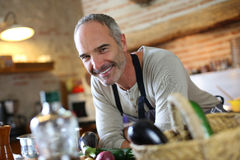 Smiling man standing in old kitchen Stock Photo