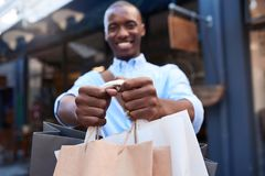 Smiling man standing outside carrying a load of shopping bags. Portrait of a stylish young African man smiling and holding up shopping bags while out shopping in stock photography