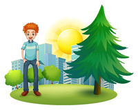 A smiling man standing beside the pine tree Royalty Free Stock Image