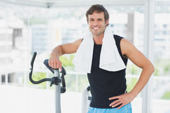Smiling man standing at spinning class in bright gym Stock Photos