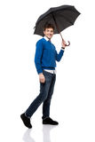 Smiling man standing under umbrella Stock Image