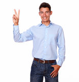 Smiling man is standing with a victory sign. Royalty Free Stock Photography