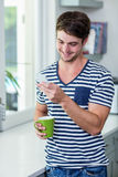 Smiling man staring at his smartphone. In the kitchen Royalty Free Stock Image