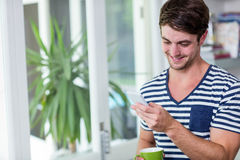 Smiling man staring at his smartphone. In the kitchen Stock Photos