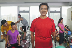 Smiling man with stopwatch in the foreground, people working out in the gym in the background Royalty Free Stock Image