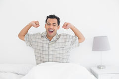 Smiling man stretching his arms in bed Stock Photo