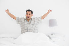 Smiling man stretching his arms in bed Stock Photos