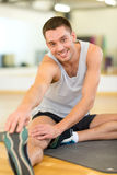 Smiling man stretching on mat in the gym Royalty Free Stock Images