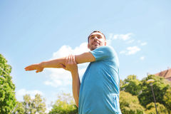 Smiling man stretching outdoors Royalty Free Stock Photography