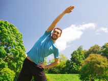 Smiling man stretching outdoors Royalty Free Stock Images