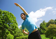 Smiling man stretching outdoors Stock Photo