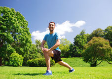 Smiling man stretching outdoors Royalty Free Stock Photos