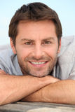 Smiling man with stubble. Closeup of a smiling man with stubble resting his head on his arms Royalty Free Stock Image