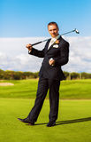 Smiling man in suit holding ball and wood Royalty Free Stock Images