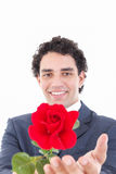 Smiling man in a suit holding a red rose and offers it to the ca Stock Photos
