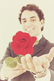 Smiling man in a suit holding a red rose and offers it to the ca Stock Image